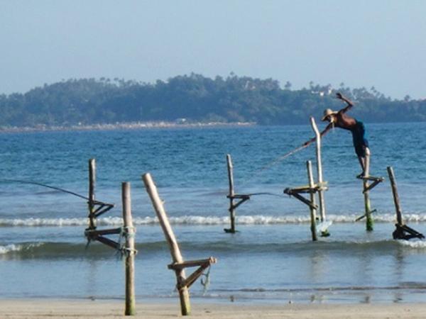 海岸線に沿いにある町アハンガマは、海中に立てた杭につかまって引っかけ釣りをするストルト・フィッシングで有名なところで、バスからも釣り風景を見ることが出来ます。写真はウェリガマのビーチで観光客に写真を撮らせるためにポーズを取っている男性。まるで魔法使いのようでした