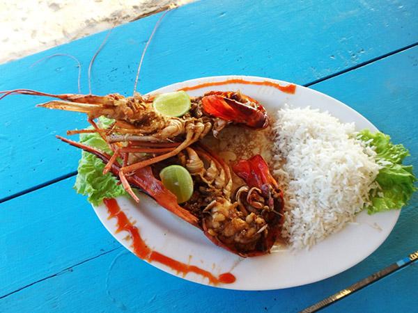 """ウェリガマのメインロード沿いには魚屋が並んでいて、買った魚介類を調理してもらえます。近くの砂浜にあるレストランで、海を見ながら楽しいディナータイム♪ """"ジャンボ"""" と呼ばれる大きなエビは調理代込みで約1,170円。イカは500gで約390円でした。意外にも味付けが良くで大満足"""