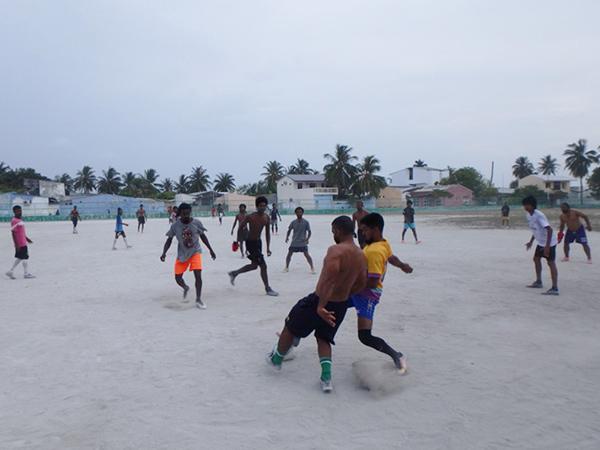 砂のグラウンドでサッカーを楽しんでいるマアフシ島の男性たち