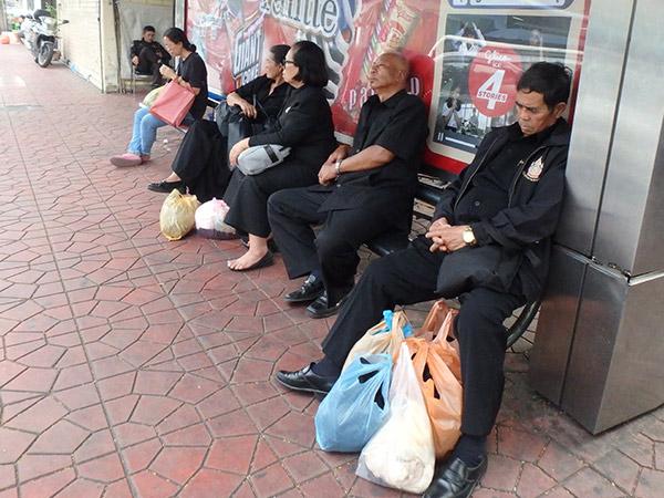 バスを待っている人々。街中は黒い服を着ている人が多い