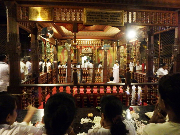仏歯寺 Dalada Maligawa の本堂で仏歯が納められている金製の豪華な容器に手を合わせる参拝者たち。仏歯の部屋が開扉されるプージャは毎日5:30、9:30、18:30の3回。外国人の入場料は1,500ルピー(約1,170円)で靴を預けるのも有料