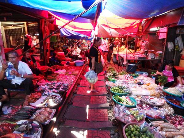 線路の上にまで商品が並べられ、カラフルな日よけがビッシリと広げられているメークロン市場