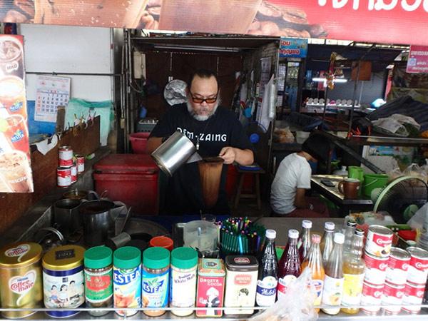 メークロン市場の中にあるドリンクスタンド。練乳がたっぷり入っているタイのアイスコーヒーを飲んで一休み