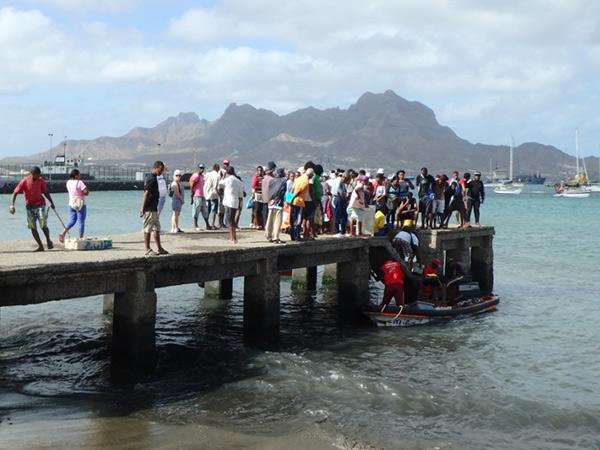 フィッシュマーケットの裏にある桟橋で、魚を運んでいる様子を眺めている人々