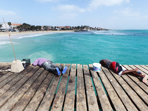 強風の中、桟橋に寝そべって釣りをしている男性たち。なんだか不思議な光景でした