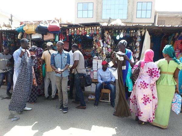 市場で歩きながらワンピースを売っている男性たち