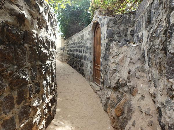 石垣に挟まれた砂の小道を歩いて島を散策