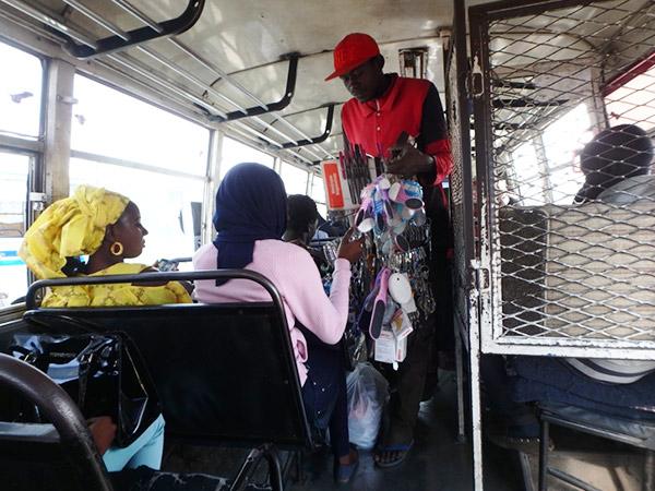 ダカールで毎日お世話になった市バス。バスターミナルに止まっている間は、次々に物売りが現れて種類の多さにビックリ! バスの運賃は、右側の金網の中にいる人に行き先を告げて支払います
