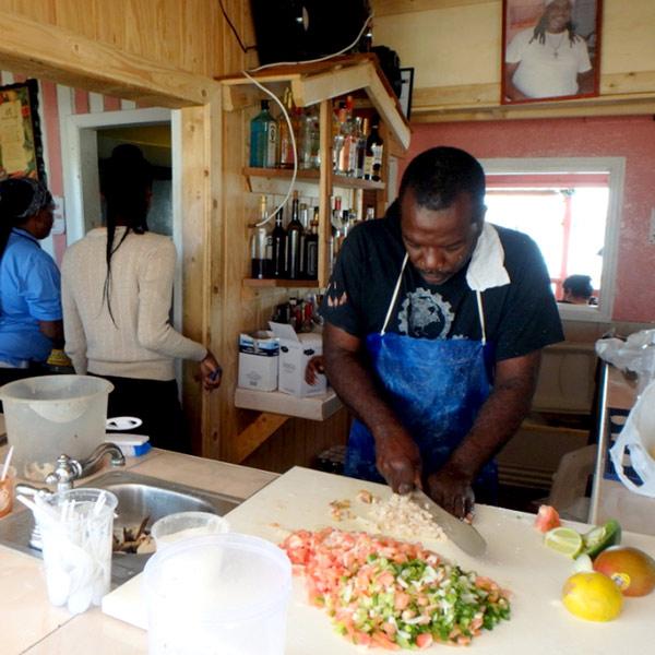 地元の人々に大人気の食堂で、コンク貝のサラダを作っている男性