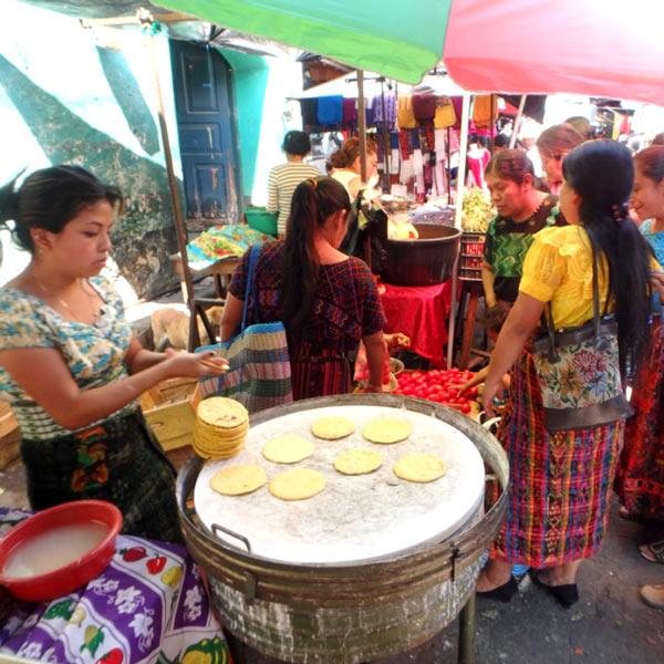 サン・ルーカス・トリマンの火曜市でトルティーヤ(トウモロコシから作る薄焼パン)を焼いている女性